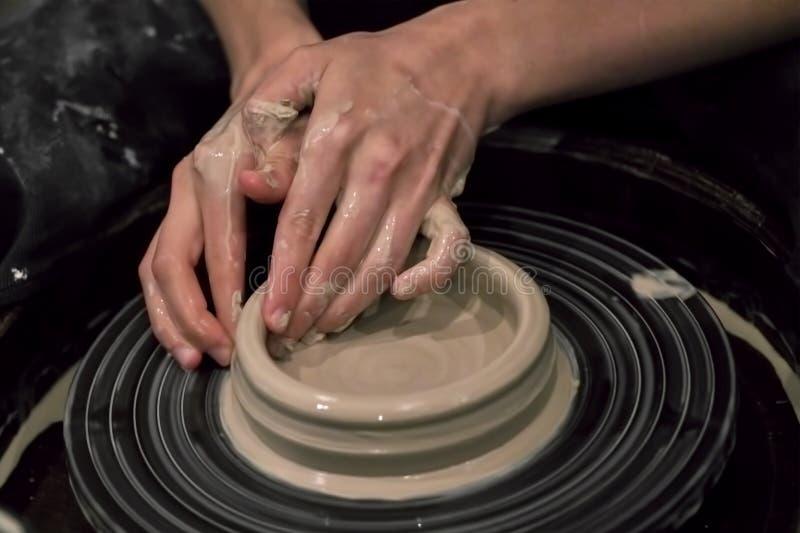 Dient klei in vormen het product op een wiel van de pottenbakker, close-up stock afbeelding