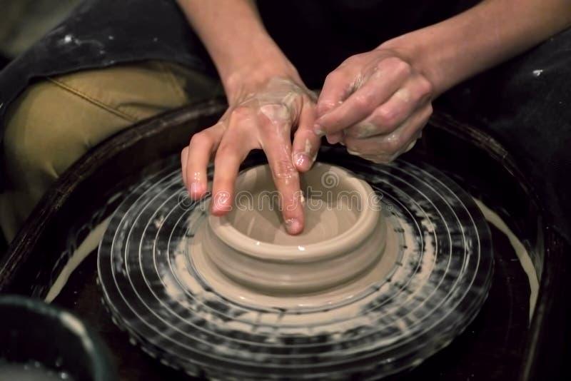 Dient klei in vormen het product op een wiel van de pottenbakker, close-up royalty-vrije stock foto