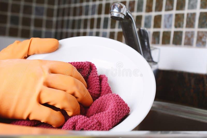 Dient rubberhandschoenen in die schotels met spon wassen stock afbeeldingen