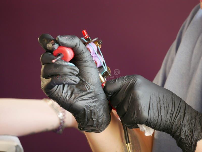 Dient zwarte handschoenen in houdend een tatoegeringsmachine stock foto's