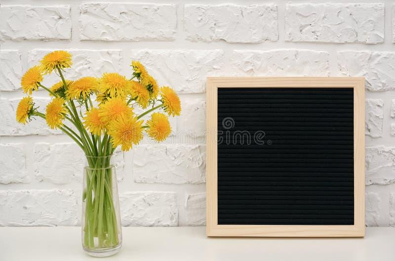 Diente de león amarillo del ramo en florero y tablero en blanco de la letra negra en la tabla contra la pared de ladrillo blanca  fotografía de archivo