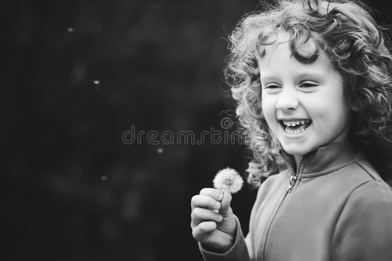 Diente de león que sopla de la pequeña muchacha rizada hermosa, p blanco y negro imagen de archivo