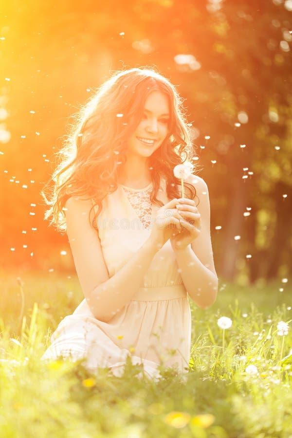Diente de león que sopla de la primavera de la mujer joven de la moda en jardín de la primavera S foto de archivo