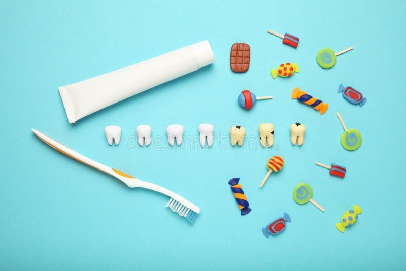 Dientes con los caramelos dulces Carie del diente en los niños, atención sanitaria dental, crema dental y cepillo de dientes fotografía de archivo libre de regalías