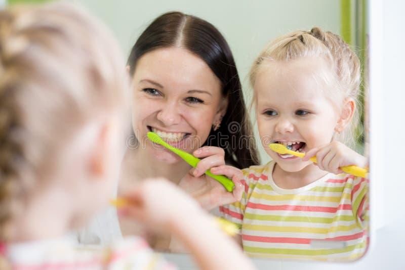Dientes de cepillado de la hija de la madre y del niño junto en cuarto de baño imagen de archivo