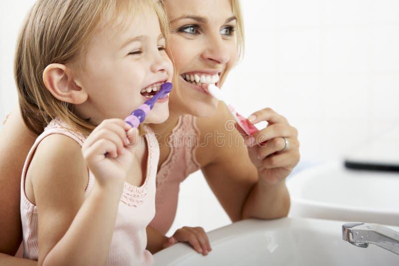 Dientes de cepillado de la madre y de la hija junto foto de archivo