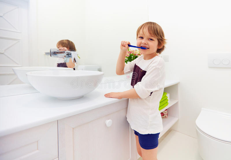 Dientes de cepillado del muchacho joven feliz en cuarto de baño imagenes de archivo