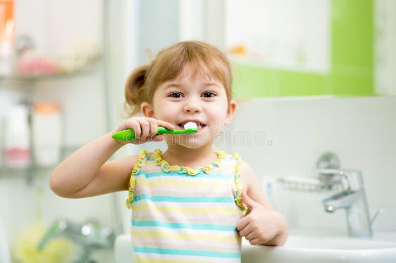 Dientes de cepillado del niño en cuarto de baño imagenes de archivo
