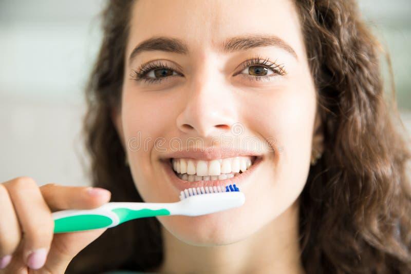 Dientes de cepillado de la mujer hermosa en clínica dental imagenes de archivo