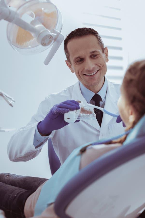 Dientes de enseñanza del feliz dentista de sexo masculino que limpian en modelo foto de archivo