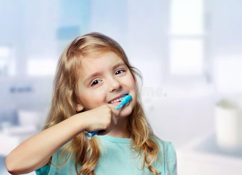 Dientes de la limpieza del niño de la muchacha del niño en fondo del cuarto de baño fotos de archivo