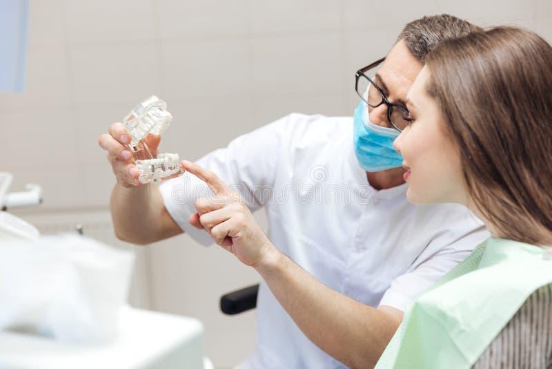 Dientes de las dentaduras de la demostración del dentista del hombre en la cirugía dental al paciente fotografía de archivo