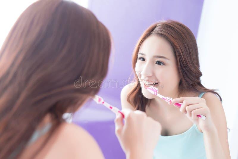 Dientes del cepillo de la mujer de la sonrisa foto de archivo