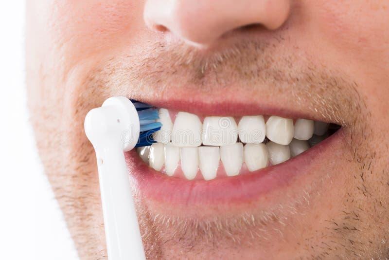 Dientes del hombre con el cepillo de dientes eléctrico foto de archivo libre de regalías