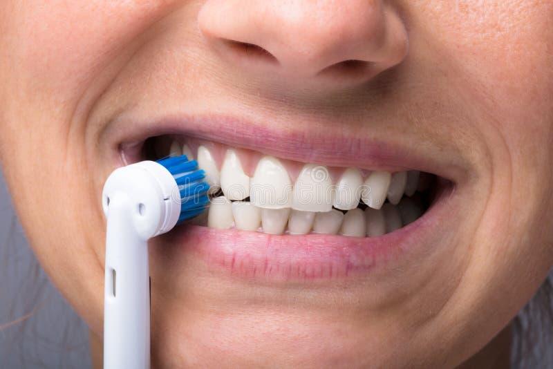 Dientes del ` s de la mujer con el cepillo de dientes eléctrico imagenes de archivo