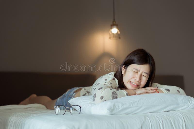 Dientes durmientes y de pulidos de la mujer asiática en el dormitorio, el cansancio femenino y la tensión fotos de archivo libres de regalías