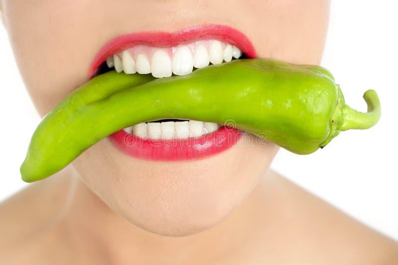 Dientes hermosos de la mujer que comen la pimienta verde fotos de archivo libres de regalías