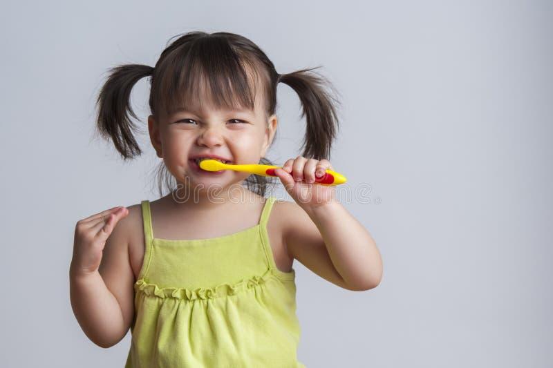 Dientes que aplican con brocha de la muchacha foto de archivo libre de regalías