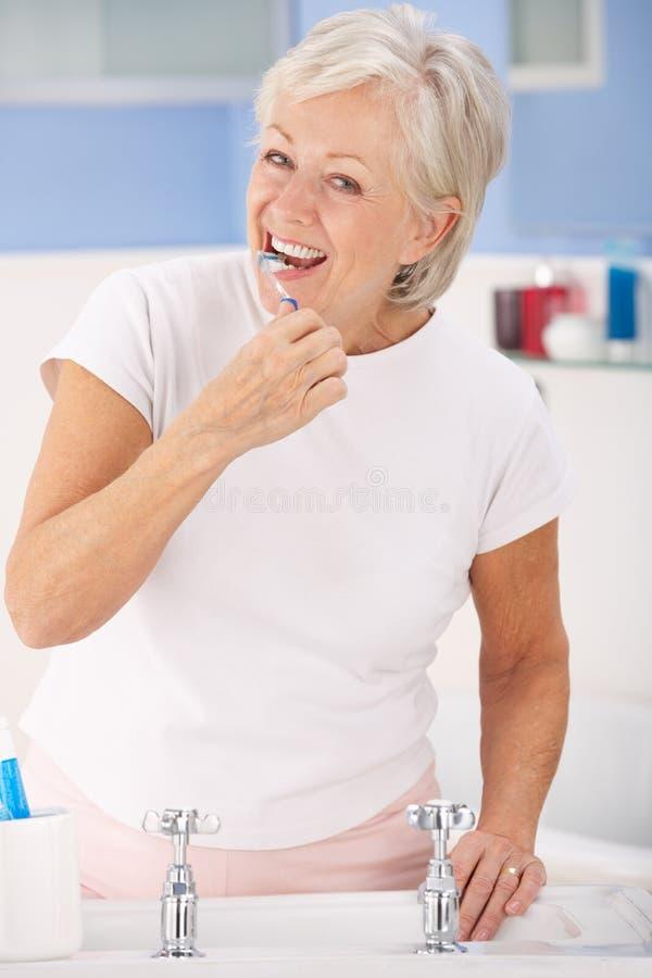 Dientes que aplican con brocha de la mujer mayor imagenes de archivo