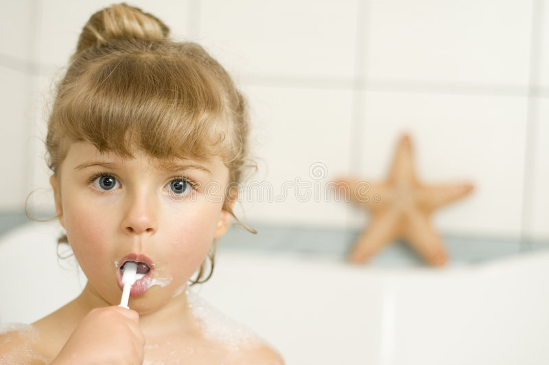 Dientes que aplican con brocha de la niña imagen de archivo