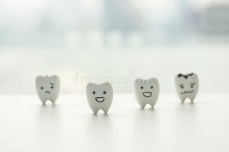 Dientes sanos e historieta decaída de los dientes con la cara sonriente y triste para la educación del niño imagen de archivo
