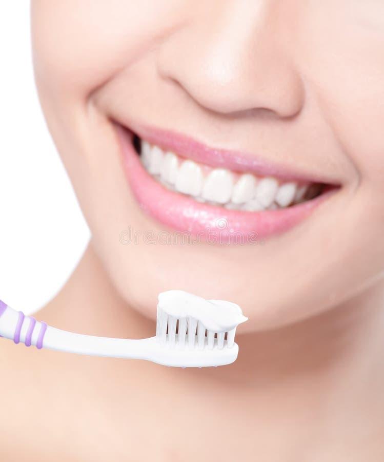 Dientes sonrientes de la limpieza de la mujer con el cepillo de dientes fotos de archivo