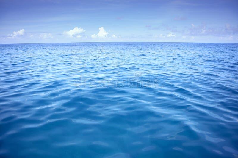 Diep blauw zeewater met witte wolk over hemel royalty-vrije stock afbeeldingen