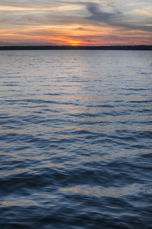 Diep Blauwe en Oranje Zonsondergang over Meer royalty-vrije stock afbeelding