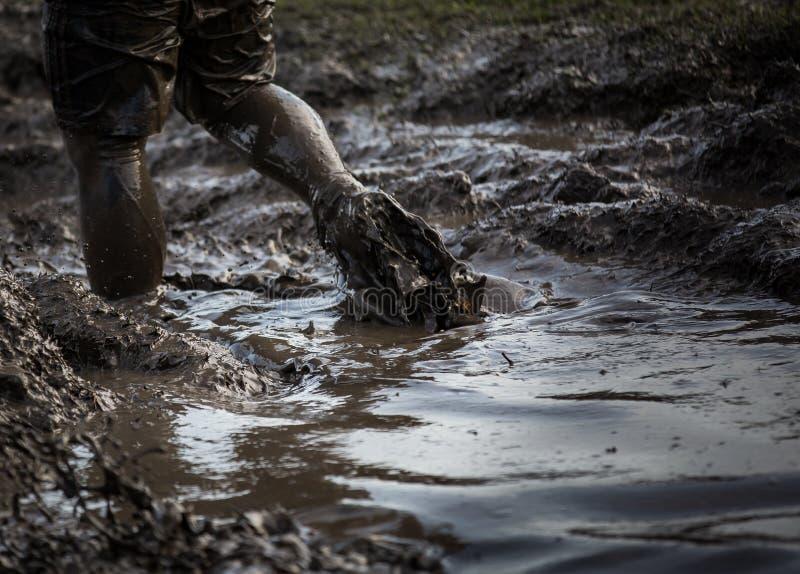 Diep modderig water met voeten die door en de modder bespatten slepen royalty-vrije stock afbeelding