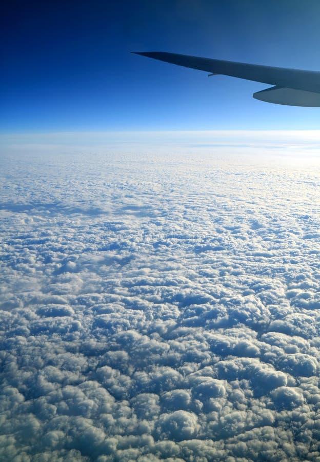 Diepe blauwe hemel en zuivere witte die wolken met vliegtuigvleugel van vliegtuigvenster tijdens de vlucht wordt gezien royalty-vrije stock fotografie