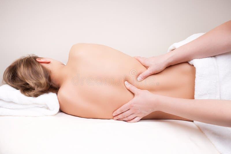 Diepe weefselmassage op de middenrug van de vrouw stock afbeelding
