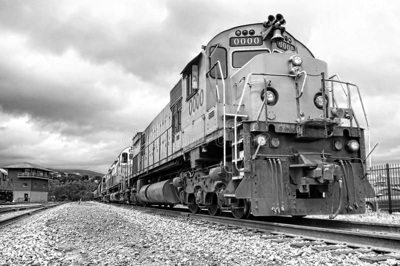 Diesel Electric Freight Train Engine Locomotives. Diesel electric freight engine locomotives marshaled in tandem pulling a cargo train riding on a rail track in royalty free stock photo
