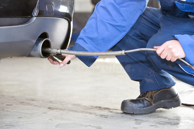 Diesel emission check. Mechanic, checking the exhaust fumes of a diesel fuelled passenger car for emission gasses, such as carbon dioxide stock photo