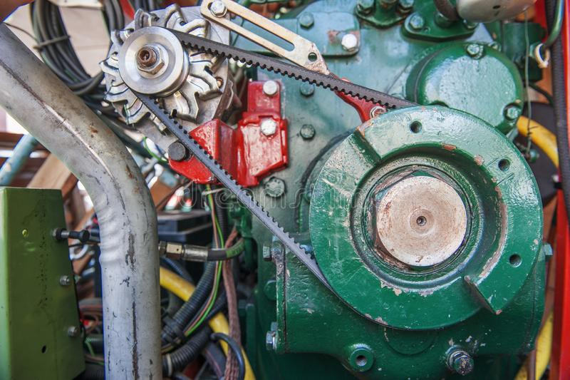 Diesel engine with alternator green. Frontal view on a diesel engine with alternator connected with timing belt stock photos