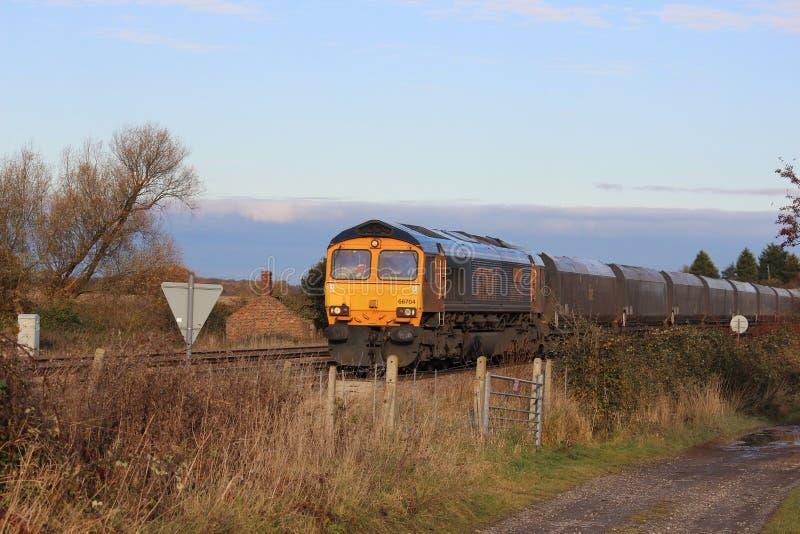 Diesel locomotief met steenkooltrein in platteland stock foto
