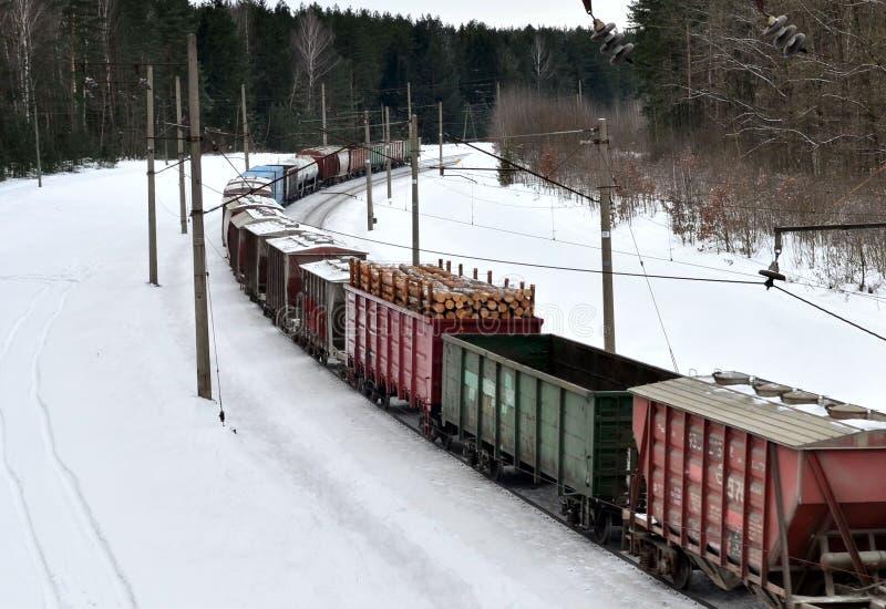 Diesel locomotief met wagens voortbewegingsritten per spoor in de winter stock afbeelding