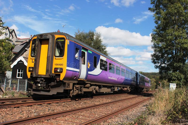 Diesel multiple unit at Grange-over-Sands, Cumbria. A class 156 dmu (diesel multiple unit) operated by Northern and in their livery heads towards a red semaphore stock image