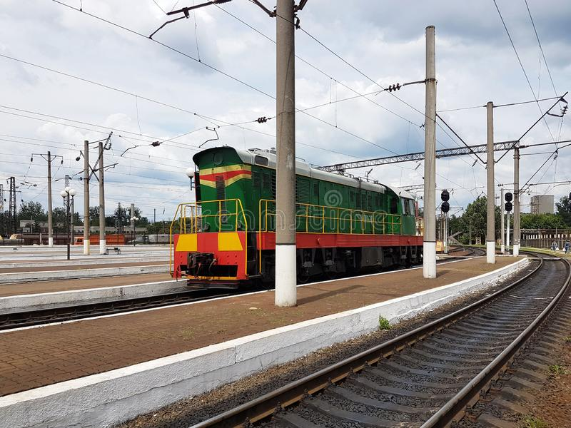 Diesel shunting locomotive of green and red colors stands near Peron. Tractor train of Soviet times. Infrastructure transport rout. Es. Powerful machine assembly stock photo