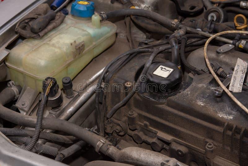 Dieselmotor in de auto en het plastic waterreservoir Vuile oude dieselmotor royalty-vrije stock afbeeldingen