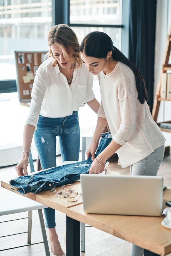 Dieses arbeitet möglicherweise Schöne junge Frauen, die Jeans und touchi betrachten stockfotos