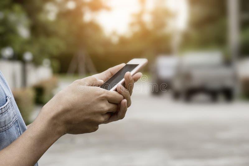 Dieses Bild ist ein Bild einer Frau, die einen Handy mit einem Haus und Autos im Hintergrund verwendet stockfoto