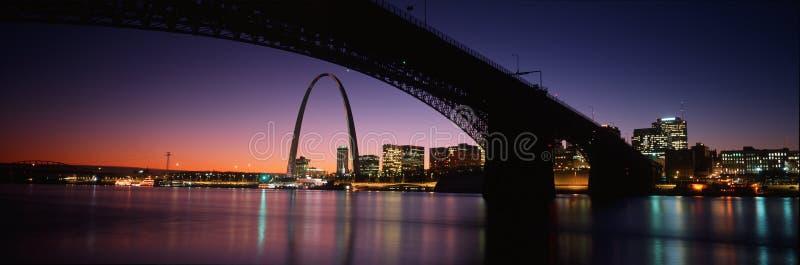 Dieses ist die Skyline und der Bogen am Sonnenuntergang Über ihr ist die Eads Brücke entlang dem Fluss Mississipi lizenzfreies stockbild