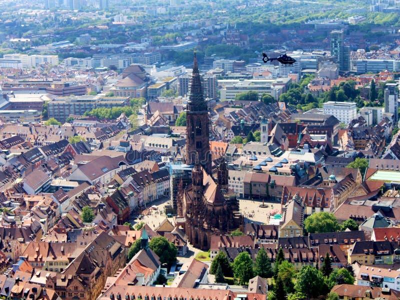 Dieses ist eine Panoramaabbildung, die die alte Münsterkirche in Freiburg, Deutschland enthalten Mit einem Hubschrauberdurchlauf  stockbild