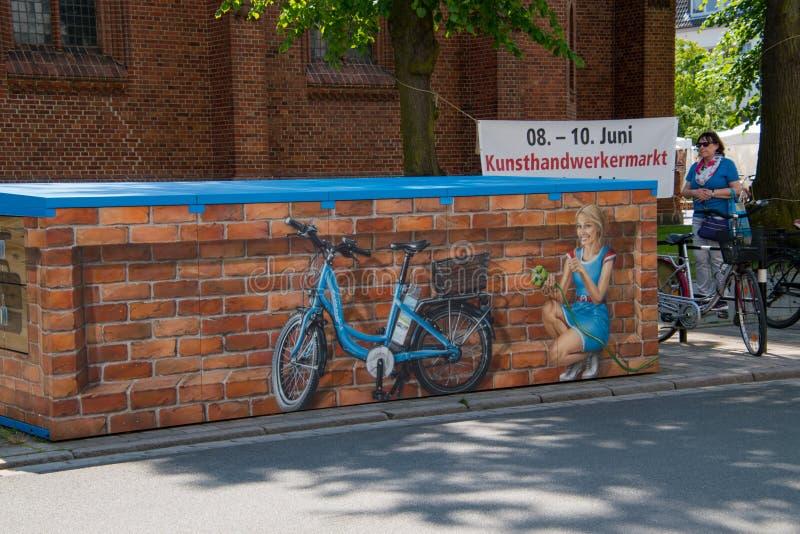 Dieses Wandgemälde, das ein recht junges Mädchen lächelt und verstopft in einem blauen elektrischen Fahrrad darstellt, wurde in d lizenzfreie stockfotografie