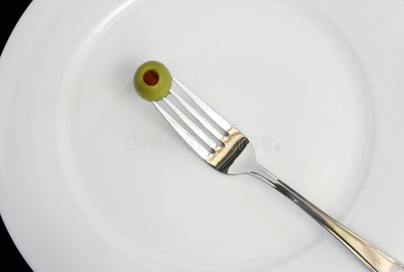On a Diet. Only one olive on a fork over a white dinner plate royalty free stock images