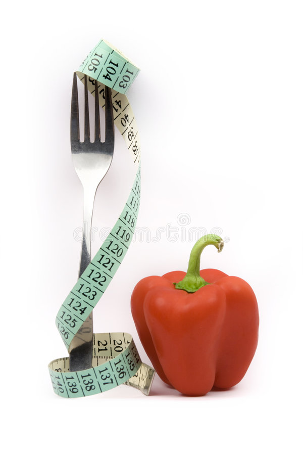 Diet. Fork with measuring-tape and red pepper - metaphor lowering (reducing) diet - grow slim stock image