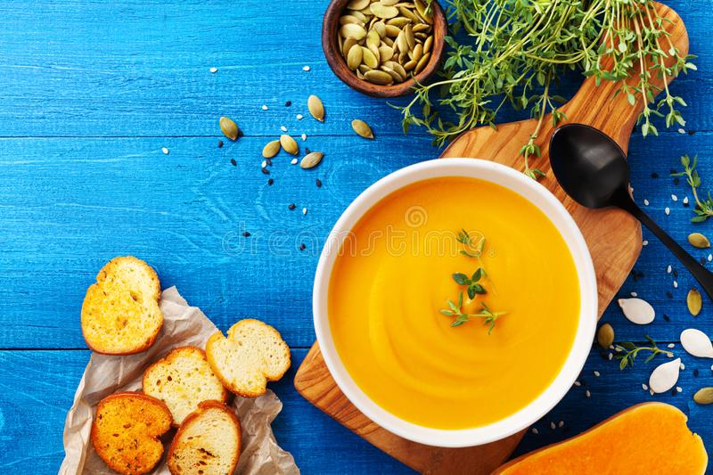 Diet autumn pumpkin or carrot cream soup in bowl served with seeds and crouton on blue rustic table top view stock photos
