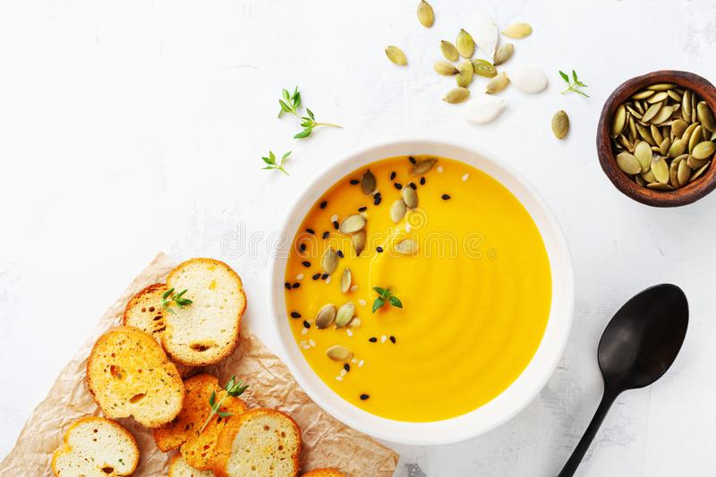 Diet autumn pumpkin or carrot cream soup in bowl served with seeds and crouton on stone table from above stock photography