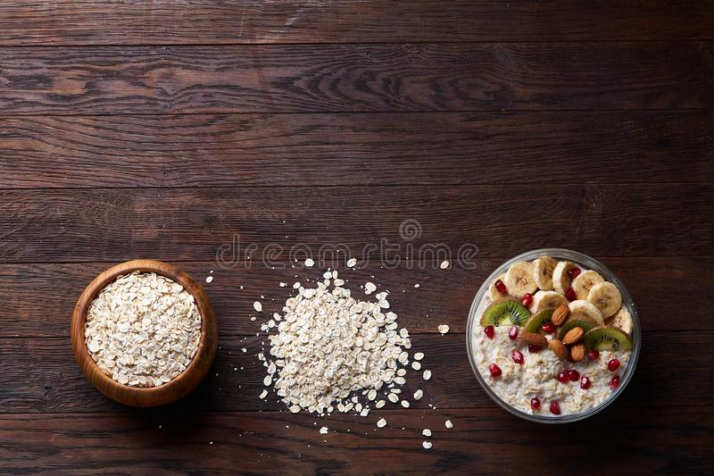 Diet breakfast oatmeal with fruits and bowl with oat flakes, selective focus, close-up stock photo
