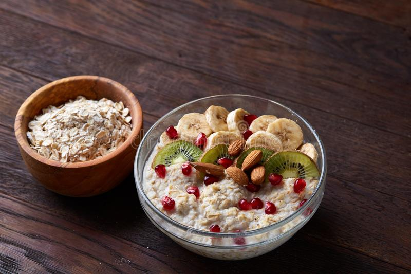 Diet breakfast oatmeal with fruits and bowl with oat flakes, selective focus, close-up stock photos